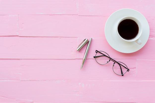 ピンクの背景にワークスペースとオフィスアクセサリーを備えたトップビューのオフィステーブル。