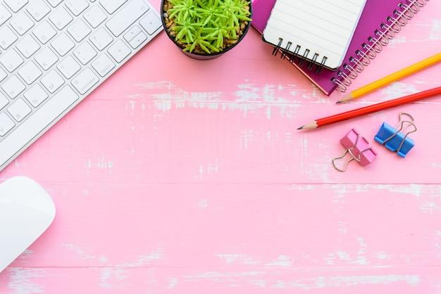 トップビューオフィステーブル、ピンクの木製の背景にワークスペース。