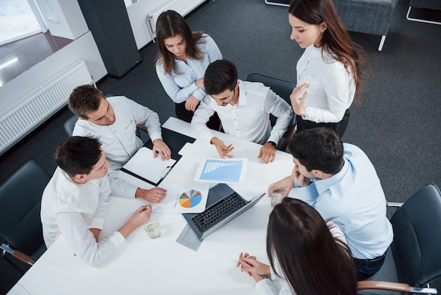 Top view of office workers in classic wear sitting near the table using laptop and documents