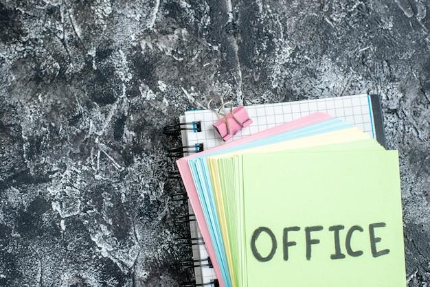 회색 배경에 다채로운 스티커와 카피 북으로 메모를 작성하는 상위 뷰 사무실