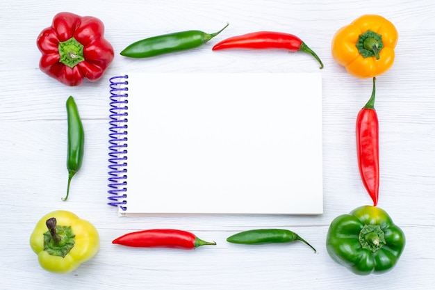 Top view offul bell-peppers lined with spicy peppers and notepad on white, vegetable spice hot food meal product