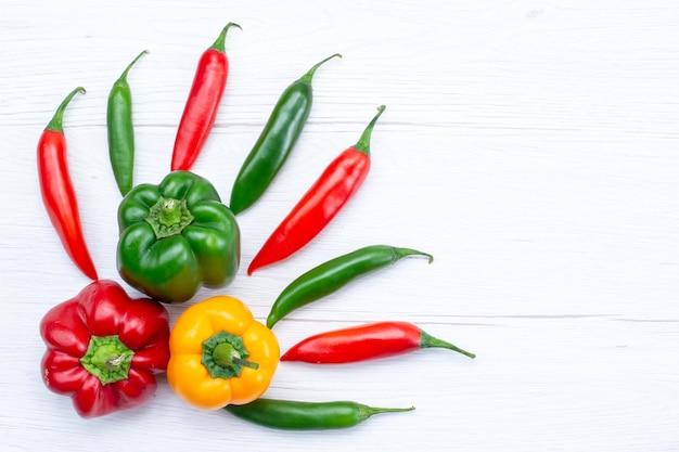 白い机の上にスパイシーなピーマン、野菜スパイスの温かい食品成分製品とフルベルペッパーの上面図