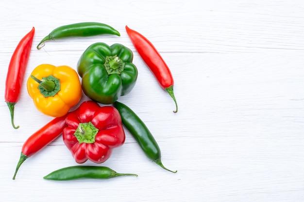 白い机の上にスパイシーな唐辛子、野菜のスパイスの温かい食べ物の食事の材料製品とフルベルペッパーの上面図