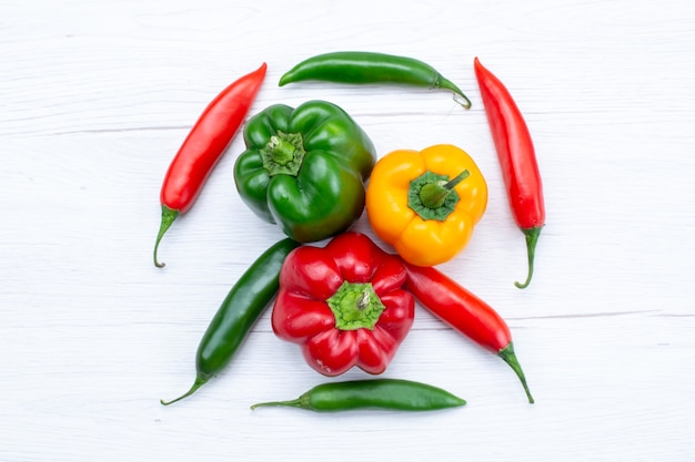Top view offul bell-peppers with spicy peppers on white, vegetable spice hot food meal ingredient product