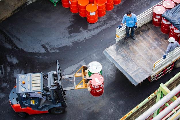 탑 뷰 오일 배럴 지게차는 운송 트럭 남성 작업자가 준비하는 데 도움을 줍니다.