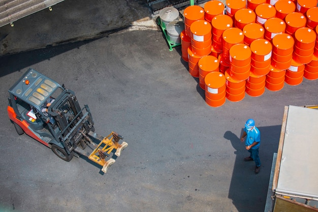 Вилочный погрузчик с нефтяными бочками, вид сверху, перемещается на транспортной тележке