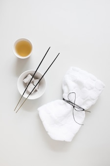 Top view of oil; incense stick; pumice stone and tied napkin on white backdrop