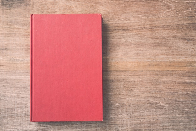 Top view old book on wooden plank background