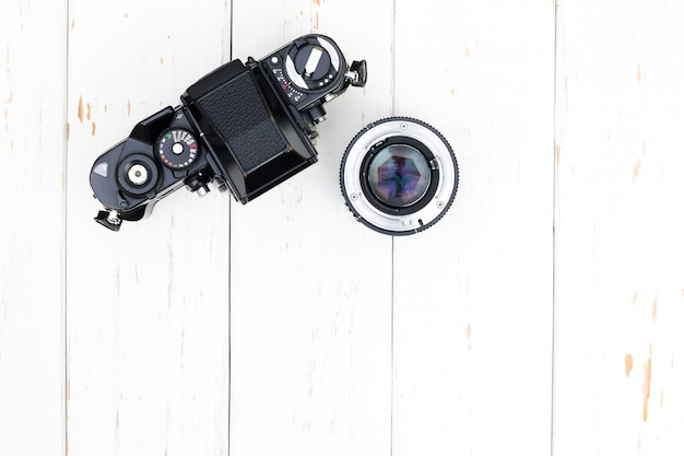 Top view of old camera body and len on white wooden background with copy space