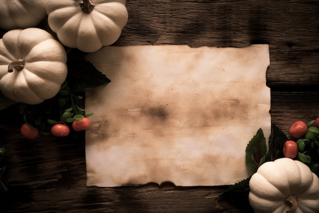 Top view of old paper with white ghost pumpkins on wooden board.