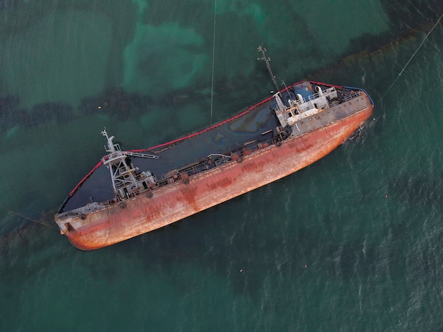 Top view of an old tanker that ran aground and overturned on the shore near the coast.