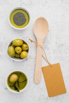 Top view olives and oil with spoon