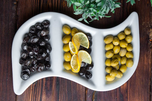 Top view olives olives with lemon on a white curly plate