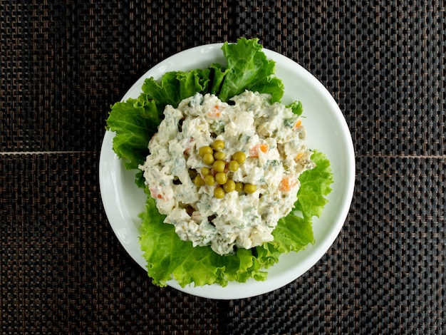 Top view of olivier salad bowl garnished with lettuce