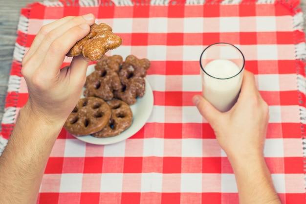市松模様のテーブルクロスの上にクッキーとミルクのガラスを保持している男の手からの上面図 Premium写真