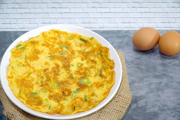 Top view of omelet (omelette, scrambled egg) with green onion on the table. asian style.