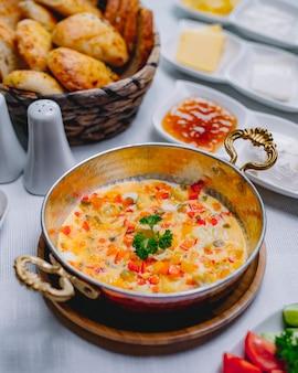 Вид сверху омлет с овощами на сковороде с корзиной хлеба
