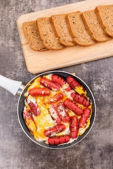 Вид сверху омлет с сосисками в сковороде овощной салат и хлеб с коричневым камнем
