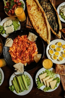 Top view omelette with tomatoes in saj with pita bread cheese cucumbers boiled eggs and juices on the table