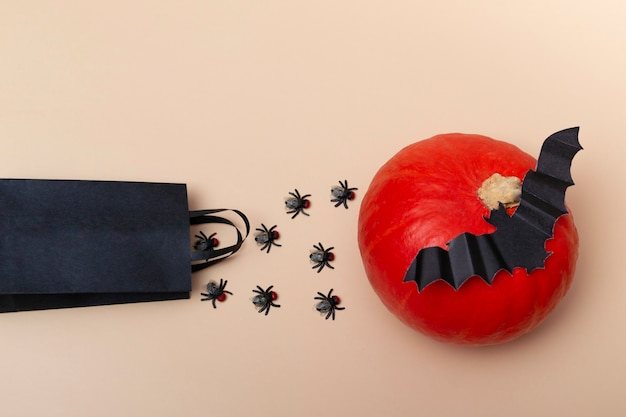 ハエ、カボチャ、コウモリとベージュの背景の黒いパッケージの上面図。ハロウィーンパーティーのクローズアップ。招待状のレイアウト。バナー