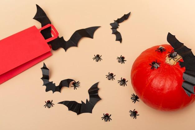 ハエ、カボチャ、コウモリとベージュの背景の赤いパッケージの上面図。ハロウィーンパーティーのクローズアップ。招待状のレイアウト