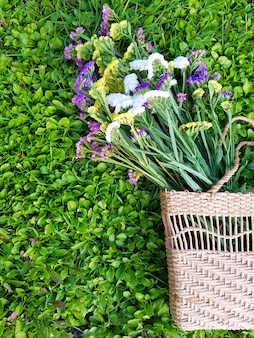 Вид сверху на букет цветов в соломенной женской сумке на фоне травы