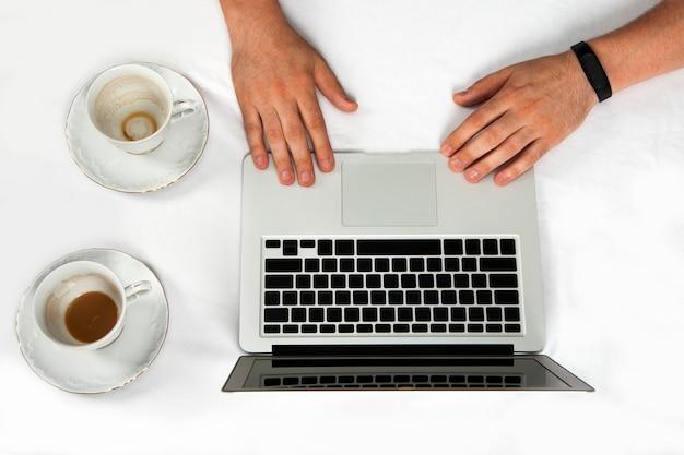 노트북으로 오랫동안 작업 해 온 사업가의 손에 상위 뷰는 흰색 배경에 격리됩니다.