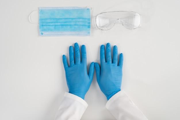 흰색 표면 의료 제품에 대한 상위 뷰 멸균 라텍스 장갑 건강 노동자를 보호하기 위해 보호 마스크 및 플라스틱 안경