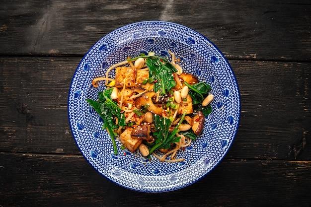 Вид сверху на азиатский жареный тофу с овощами, грибами шиитаке на деревянном столе