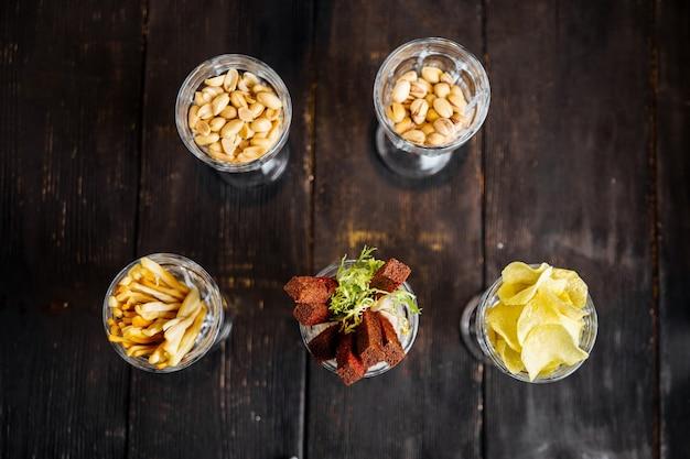 Вид сверху на различные соленые закуски пивного бара в очках на темном деревянном столе