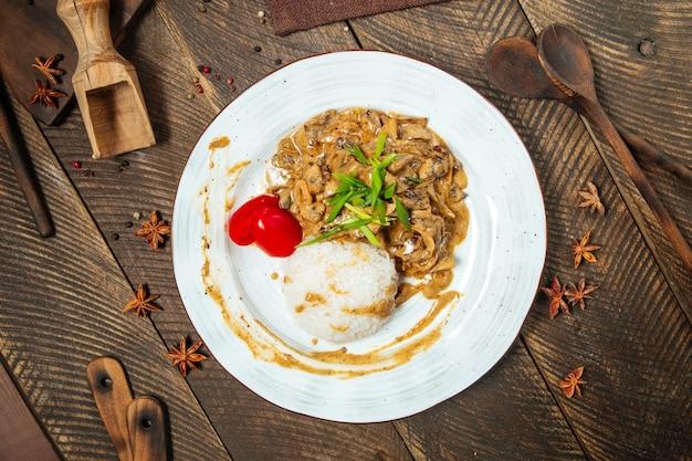 Вид сверху на бефстроганов с рисом на деревянном столе