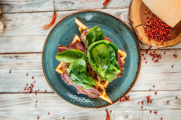 木製テーブルの上の牛のパストラミと野菜のベルギーワッフルのトップビュー