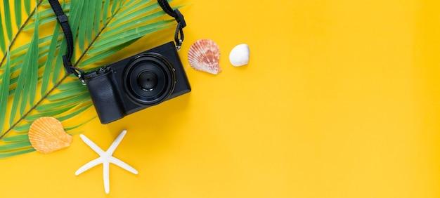 여름 동안 노란색 배경 위에 녹색 열대 잎과 껍질이 있는 검은색 카메라의 상위 뷰