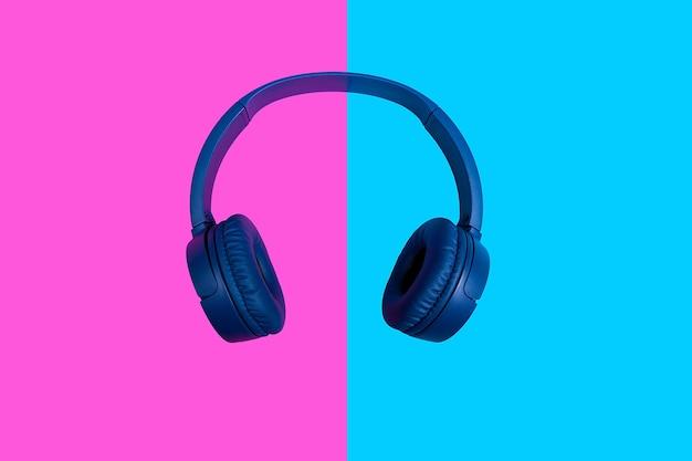 Вид сверху на голубые беспроводные наушники на ярком цветном фоне. плоский минималистичный стиль. дизайн и расцветки