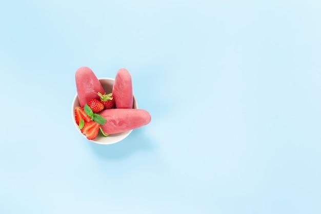 フルーティーなピンクの冷凍シャーベットアイスクリームとイチゴ、青い背景のミントとプラスチックスティックのボウルの上面図。アイスクリームの形でヨーグルトと冷凍ミックスフルーツ。子供たちはそれをたくさん食べるのが大好きです