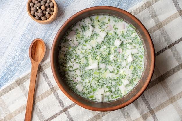Вид сверху на чашу с окрошкой. холодный суп из кваса или сыворотки с разными травами и мелко нарезанным мясом или рыбой. русская кухня.