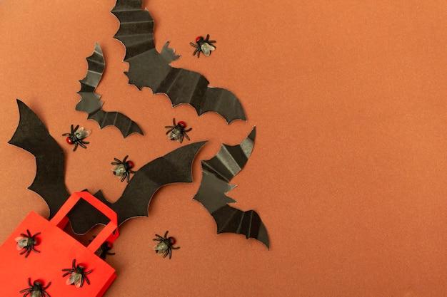 ハエとコウモリと茶色の背景の赤いパッケージの上面図。ハロウィーンパーティーをクローズアップ