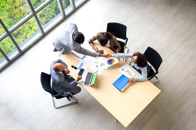 Вид сверху на рукопожатие деловых людей над документами на столе на встрече.