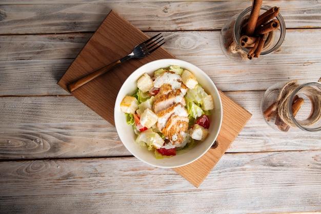 Вид сверху на салат цезарь с курицей на деревянной доске