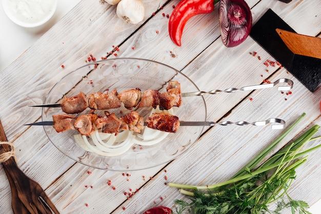 Вид сверху на кавказский шашлык из мяса на гриле на светлом деревянном столе