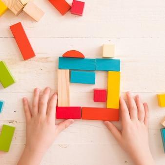 Вид сверху на детские руки, играющие с разноцветными деревянными кирпичами на фоне белого стола