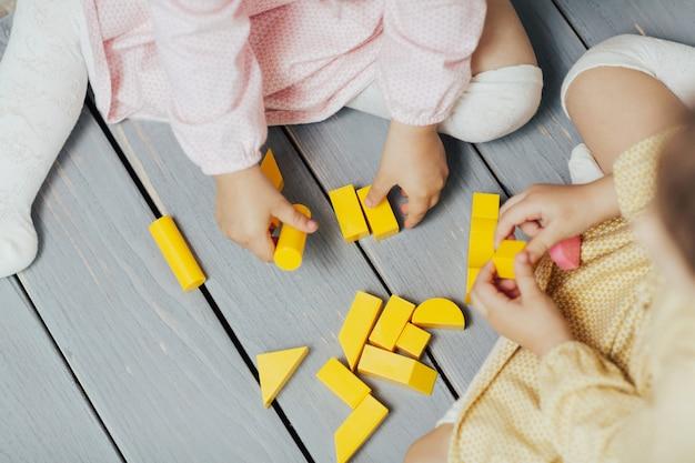 Вид сверху на детские руки, играющие с красочными желтыми блоками