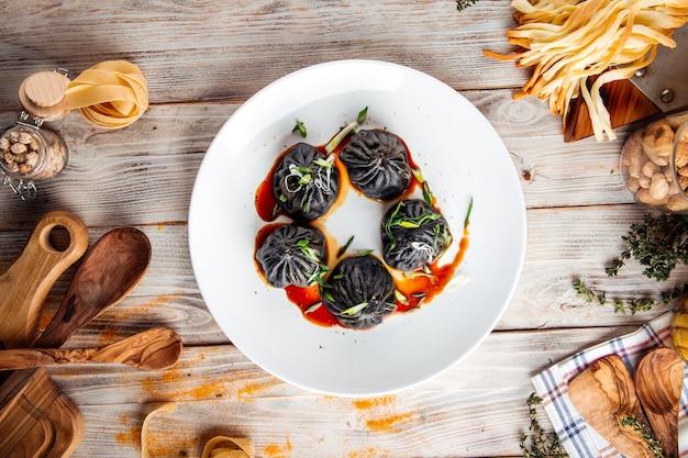 Вид сверху на китайские черные пельмени с соевым соусом и зеленым луком