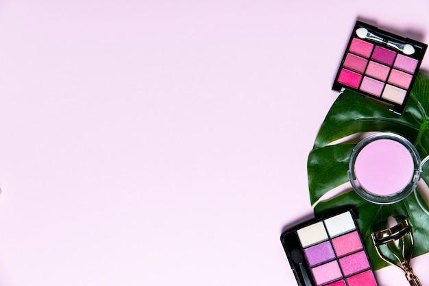 コピースペースとピンクの背景の化粧品のトップビュー
