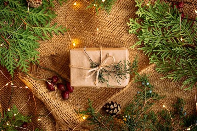 Вид сверху на подарочную коробку на деревянном столе с гирляндой и еловыми ветками
