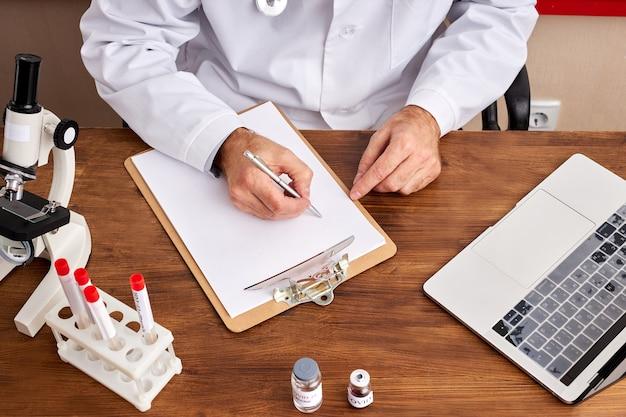 자른 의사가 테이블에 앉아 메모를 작성하고 노트북을 사용하여 코로나 바이러스 테스트 튜브로 연구하십시오.