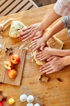 파이 또는 쿠키 반죽을 롤아웃하는 방법을 보여주는 딸을 보여주는 자른 어머니의 상위 뷰, 작은 귀여운 아이 아이 학습 머핀은 가벼운 부엌에서 행복한 엄마와 함께 조리 과정을 금지합니다.