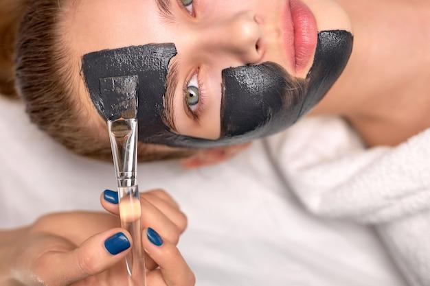 탄소 껍질을 위해 아름다운 편안한 백인 여성의 신선한 얼굴에 검은 마스크를 바르는 자른 전문 미용사에 대한 상위 뷰. 피부 관리, 웰빙, 스파, 미용 개념. 복사 공간