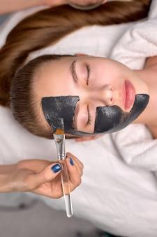 탄소 껍질을 위해 아름다운 여성의 신선한 얼굴에 검은 마스크를 바르는 자른 전문 미용사에 대한 탑 뷰, 여성은 눈을 감고 침대에 누워 있습니다. 피부 관리, 웰빙 개념입니다. 복사 공간
