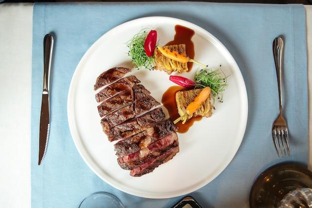 Вид сверху на нарезанный стейк рибай из говядины с картофелем на белой тарелке